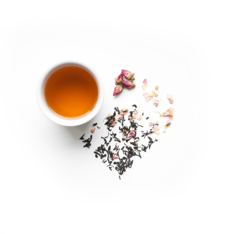 Earl Grey tea leaves in the shape of a heart beside a cup of brewed tea